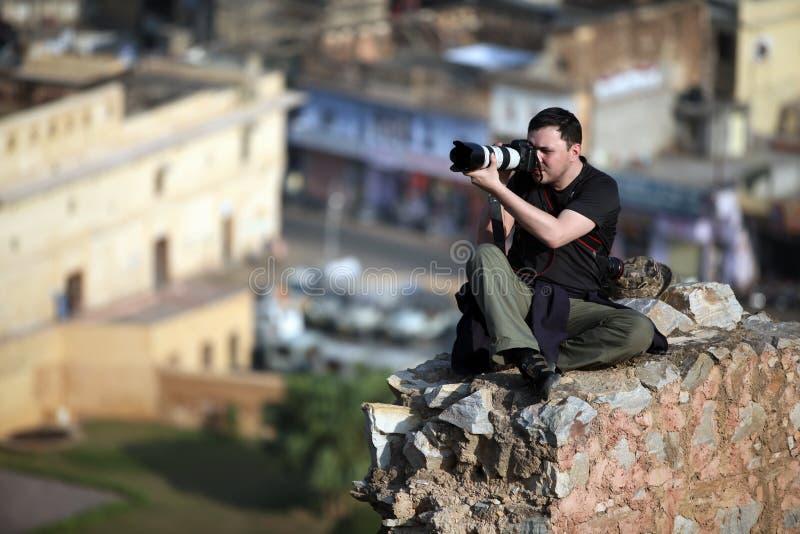 O fotógrafo que senta-se em uma rocha altamente acima dos blocos de cidade e remove a cidade índia fotografia de stock