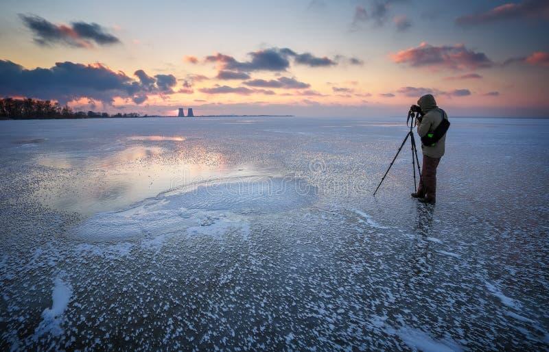 O fotógrafo toma uma imagem do por do sol em um rio congelado fotografia de stock