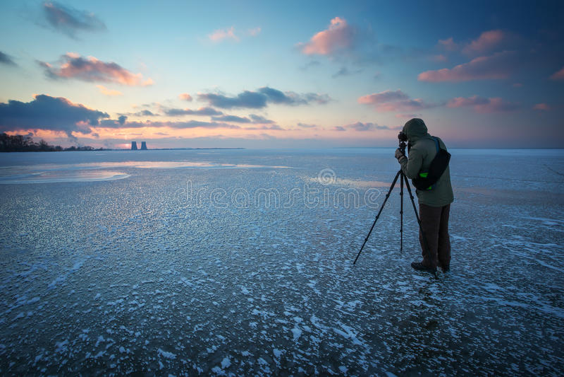O fotógrafo toma uma imagem do por do sol em um rio congelado fotos de stock royalty free
