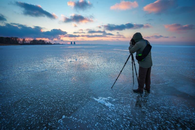 O fotógrafo toma uma imagem do por do sol em um rio congelado imagens de stock