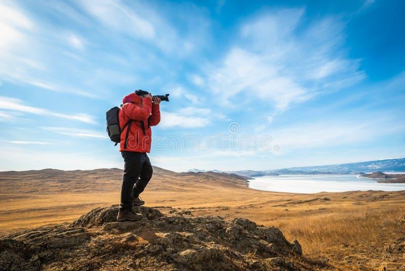 O fotógrafo veste a roupa vermelha toma a montanha e o Lago Baikal da foto no dia em Sibéria, Rússia imagens de stock