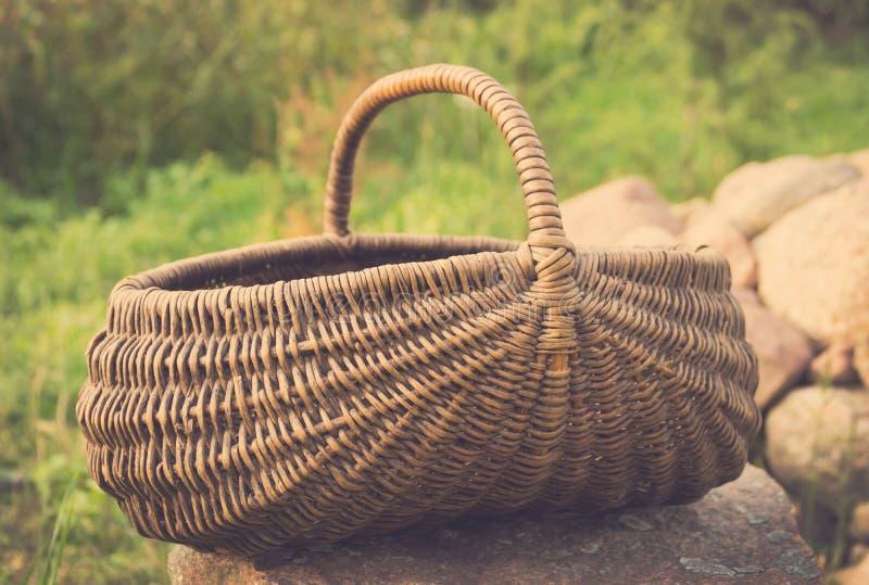 O foto do vintage da cesta vazia/trançou a cesta da cesta no gramado verde fotografia de stock royalty free