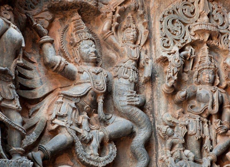 O fragmento da pedra cinzelou o relevo com o Garuda que luta uma serpente do mito Templo indiano sul do século XII Halebidu, Índi fotos de stock royalty free