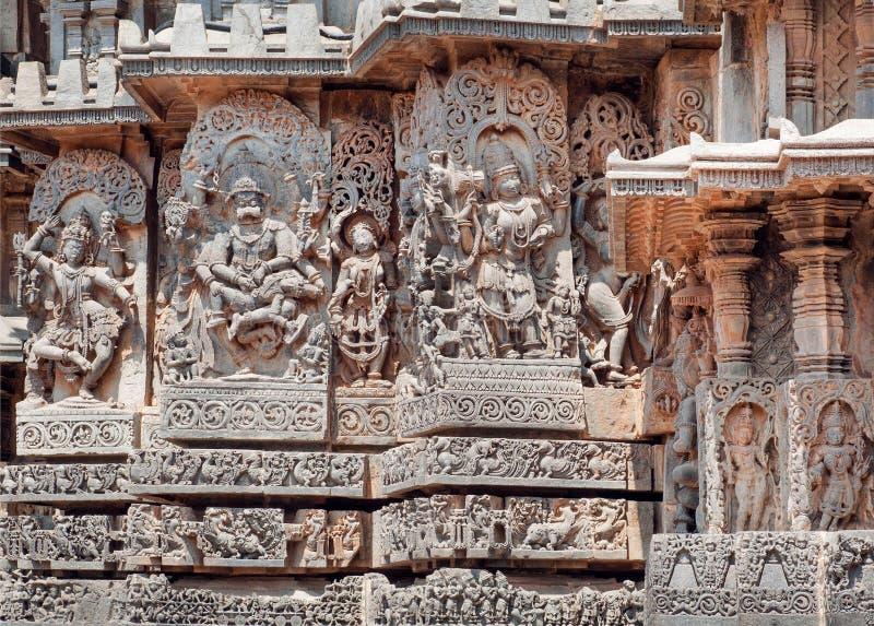 O fragmento da pedra cinzelou o relevo com Kali, Narasimha e outros deuses hindu Templo indiano do século XII Halebidu, Índia fotografia de stock