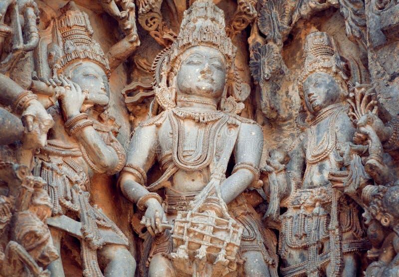 O fragmento da pedra cinzelou o relevo com os músicos que jogam a música dos deuses Templo indiano sul do século XII Halebidu, Ín imagens de stock royalty free