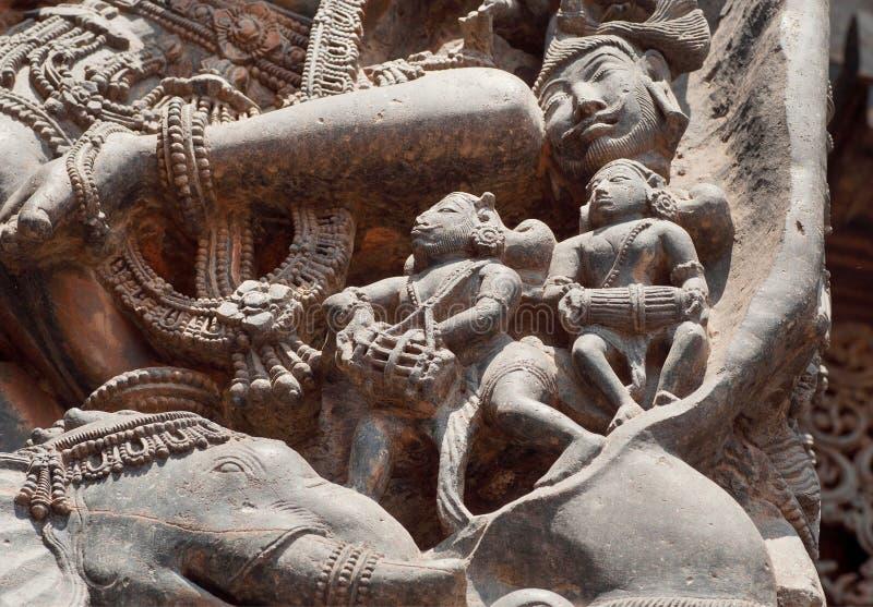 O fragmento da pedra cinzelou o relevo com os músicos sob os pés de Shiva Templo indiano sul do século XII Halebidu, Índia foto de stock