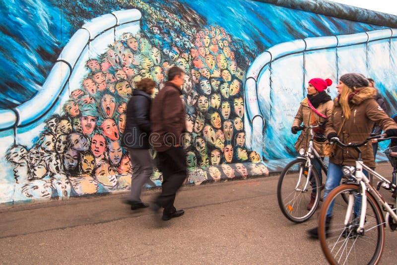 O fragmento dos grafittis em Berlin Wall na galeria da zona leste, que desmoronou em 1989 e agora é a galeria a maior dos grafitt fotografia de stock royalty free