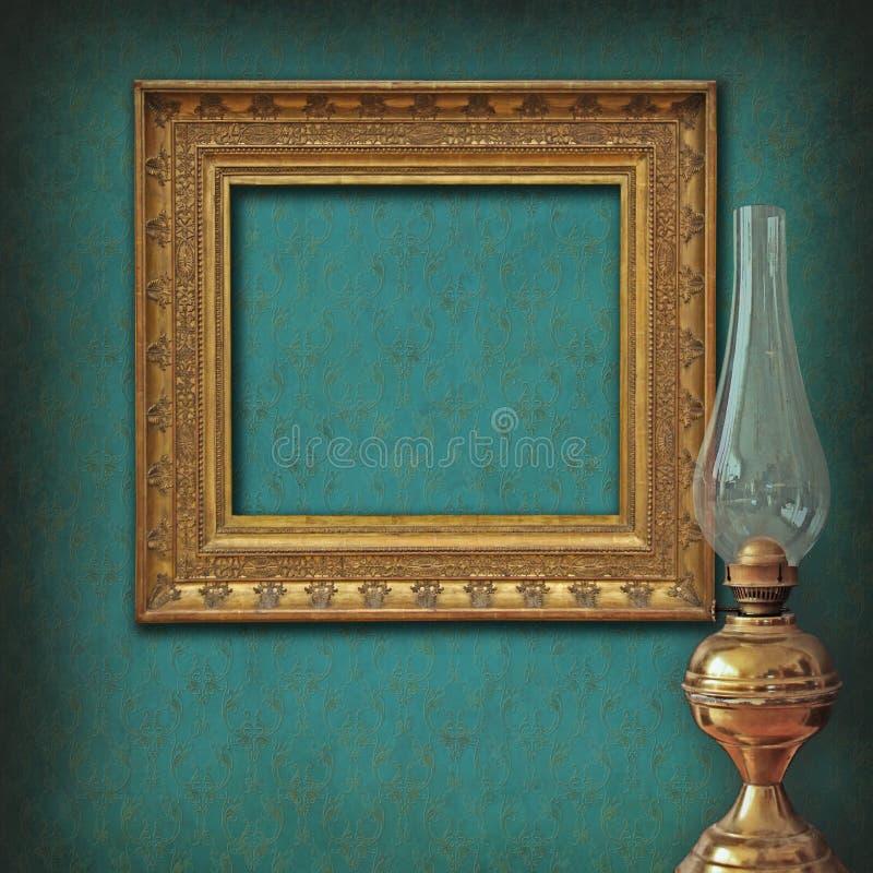 O frame vazio no papel de parede do vintage e o petróleo do bronze lam fotos de stock