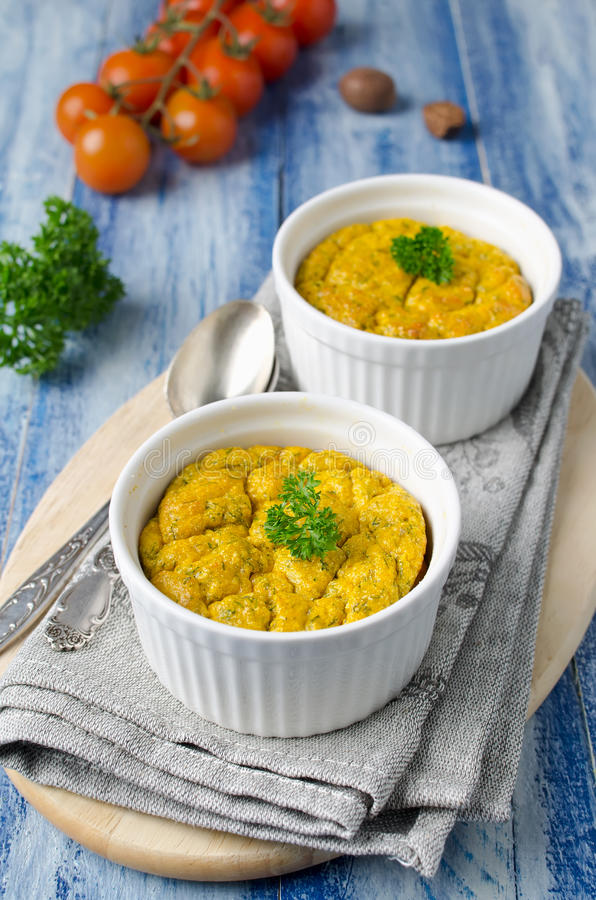 O francês cozeu o souffle de queijo com cenouras e aneto no ramek branco foto de stock