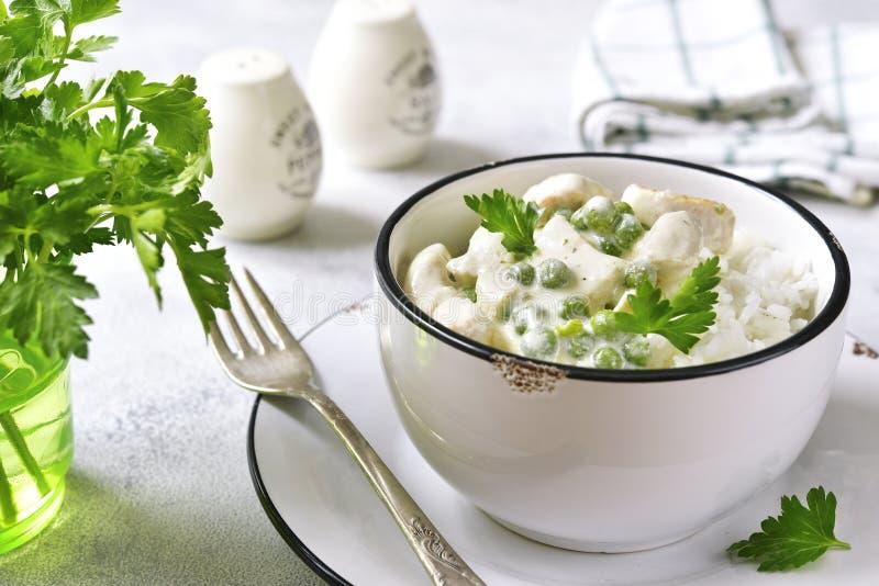 O frango de fricassê com ervilha verde serviu com arroz fervido imagens de stock