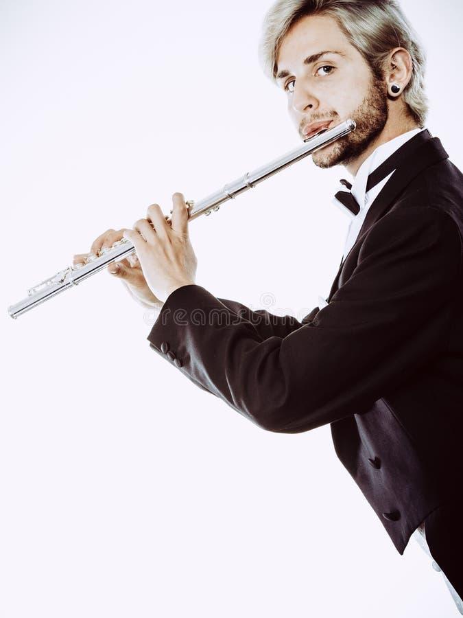 O fraque vestindo do flautista masculino joga a flauta imagens de stock