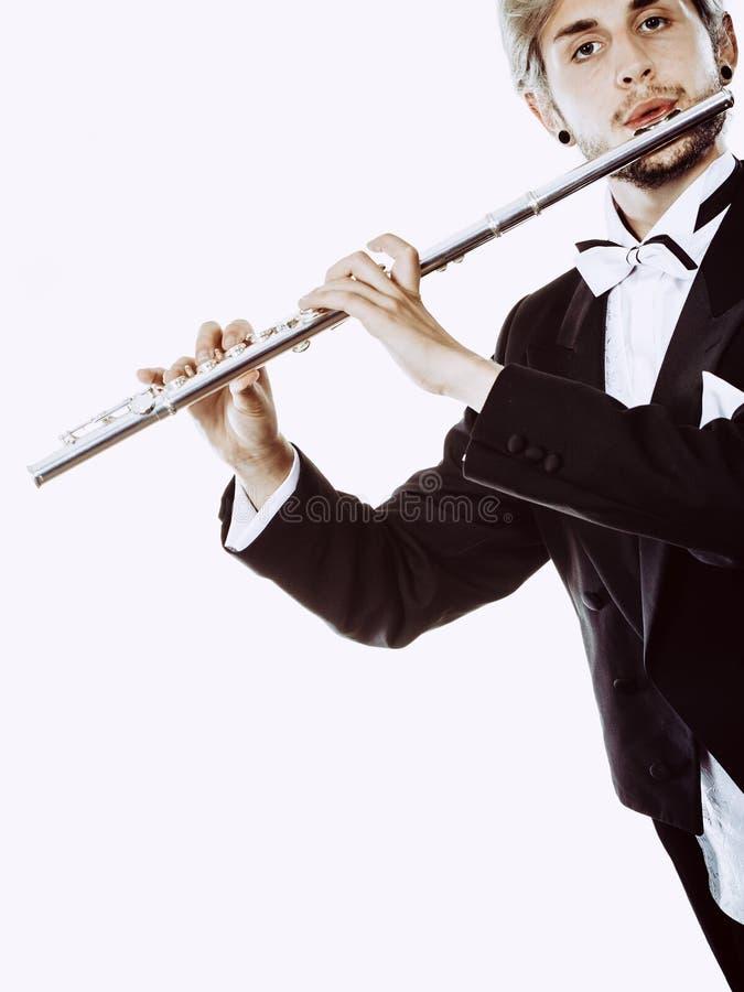O fraque vestindo do flautista masculino joga a flauta imagem de stock royalty free
