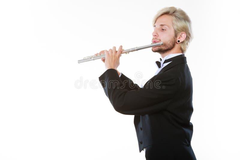 O fraque vestindo do flautista masculino joga a flauta foto de stock