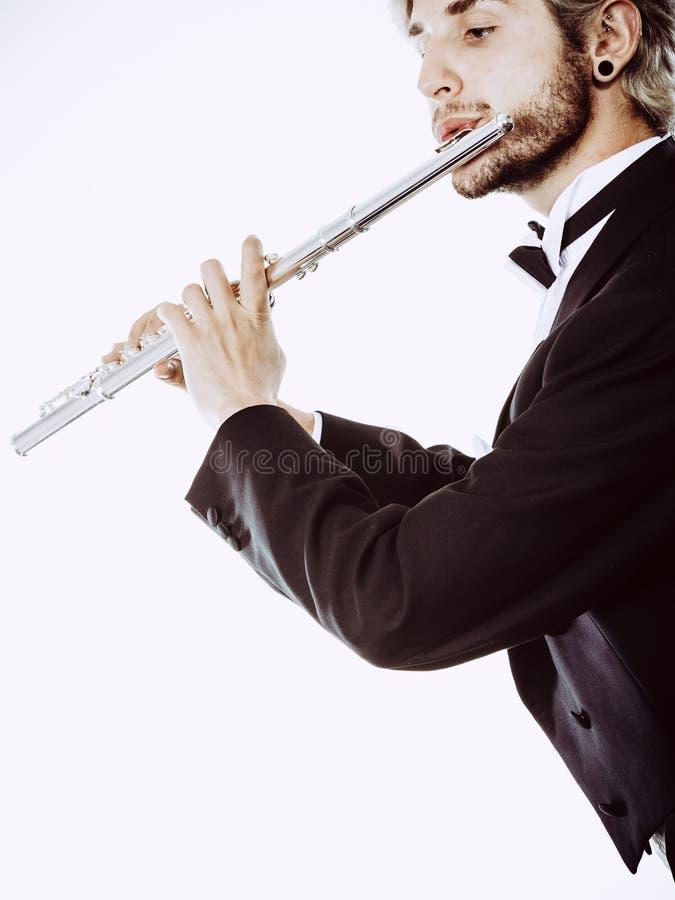 O fraque vestindo do flautista masculino joga a flauta fotografia de stock