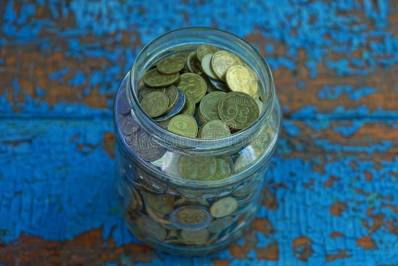 o frasco completamente de moedas pequenas está em uma tabela gasta azul foto de stock