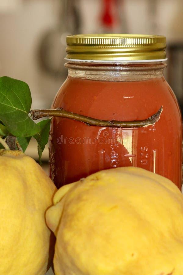 O frasco de colocação em latas de vidro encheu-se com o molho do fruto do marmelo foto de stock