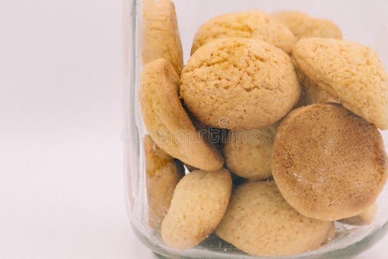 O frasco de cookie, frasco de vidro simples encheu-se com as cookies antiquados fora do fundo branco fotos de stock royalty free
