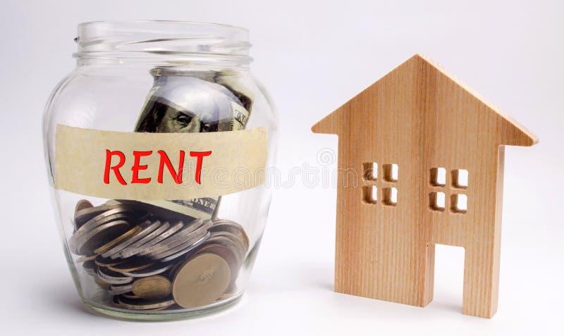 O frasco de vidro com as palavras aluga e uma casa de madeira O conceito do dinheiro de salvamento para o alojamento alugado Dinh imagem de stock