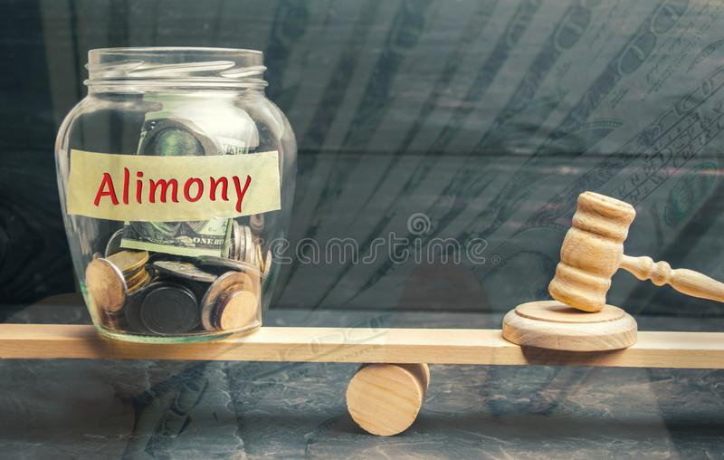 O frasco de vidro e a inscrição 'pensão alimentar 'e o martelo do juiz estão nas escalas Pagamento de uma pensão alimentar de um  imagem de stock royalty free