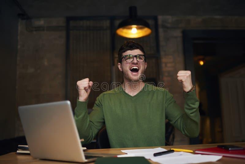 O freelancer emocional no revestimento verde no laptop conectou ao Internet sem fio no escritório fotografia de stock royalty free