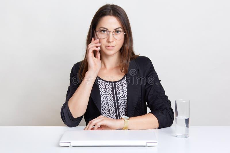 O freelancer fêmea aprecia o trabalho distante em casa, tem a conversação telefônica, senta-se na mesa branca perto do laptop e d fotografia de stock