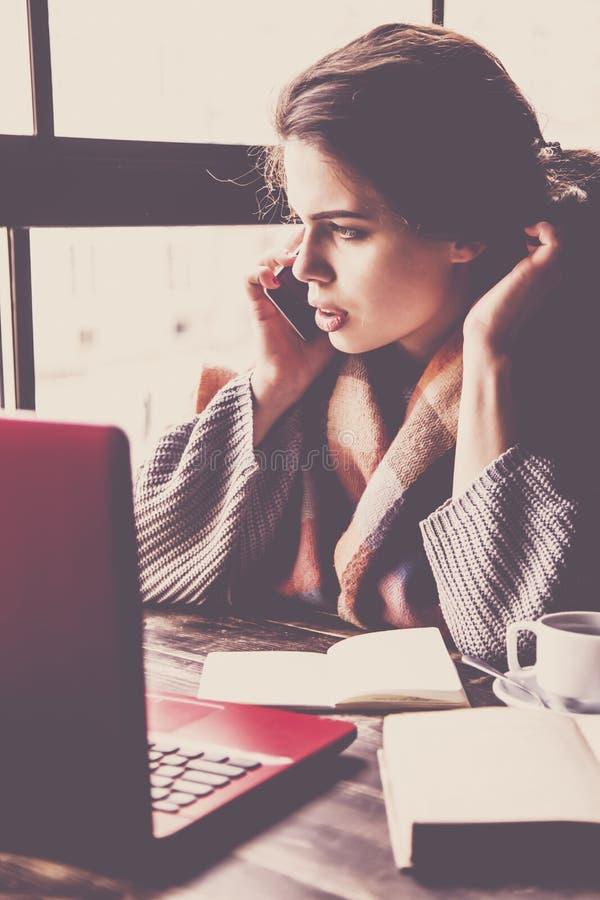O freelancer fêmea bonito fala o telefone e pelo trabalho remotamente com o portátil no café Mulher de negócio que trabalha em li imagens de stock royalty free