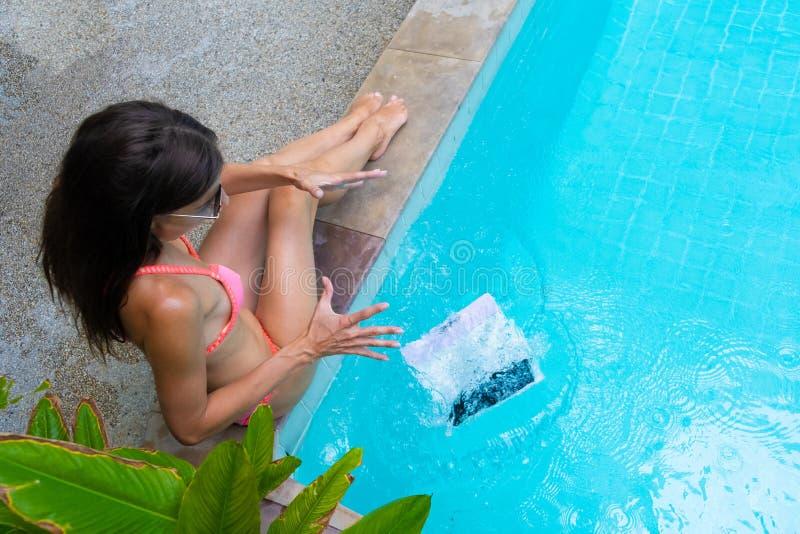 O freelancer fêmea senta-se pela associação e trabalha-se em um minicomputador, a menina deixa cair seu portátil na água Ocupado  imagens de stock royalty free