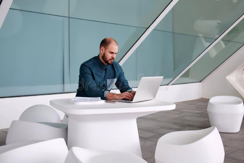 O freelancer masculino experiente cria o projeto novo do Web site no laptop ao se sentar no interior moderno do escritório, imagem de stock