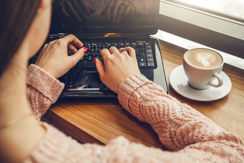 O freelancer novo aprecia o café no café usando um portátil imagem de stock royalty free