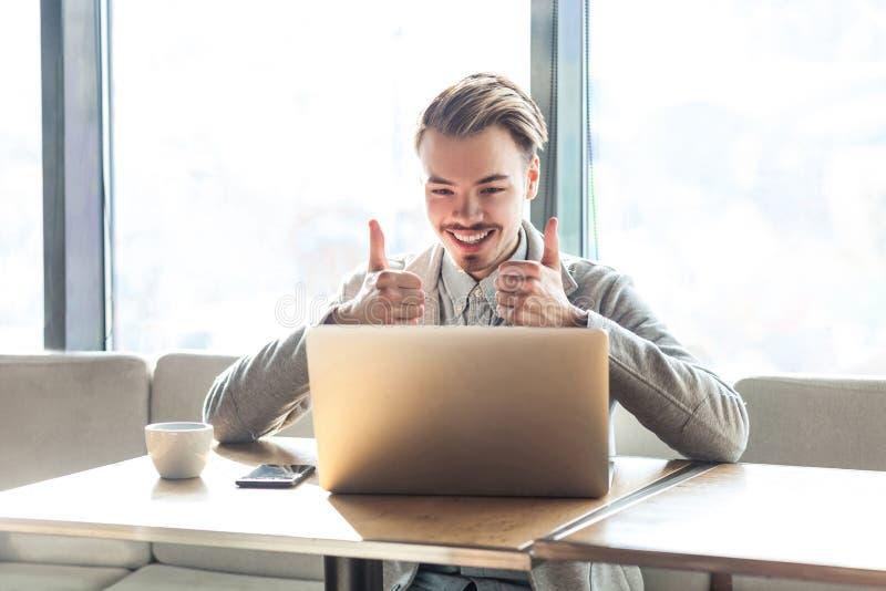 O freelancer novo positivo satisfeito considerável no blazer cinzento está sentando-se no café, olhando no portátil com sorriso e fotografia de stock