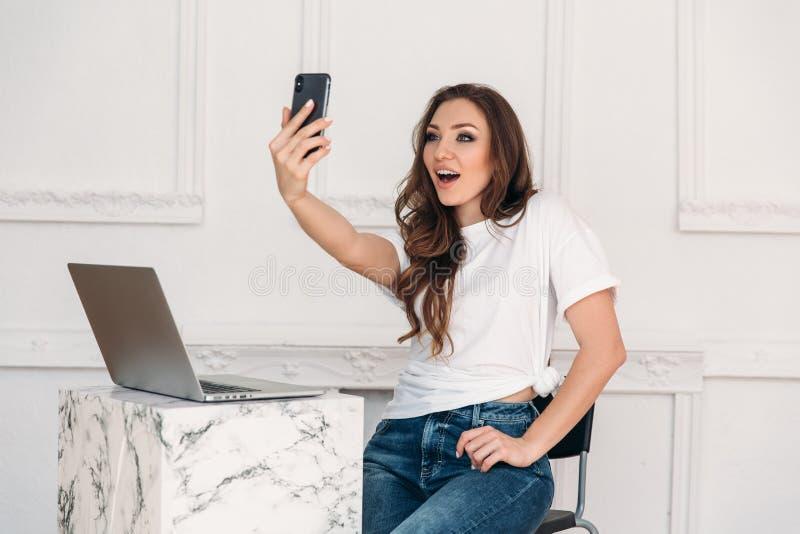 O freelancer surpreendido da menina com um portátil e um telefone em sua mão faz o selfie Jovem mulher com um t-shirt branco e as fotos de stock royalty free