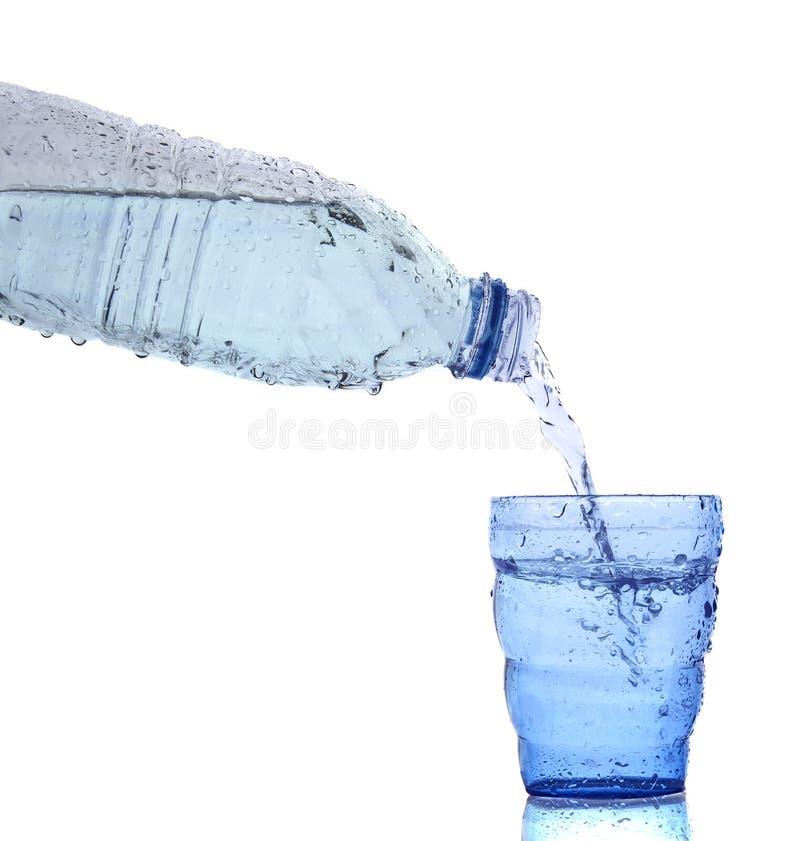 O frescor fresco e a água potável limpa que derrama ao vidro azul são fotografia de stock royalty free