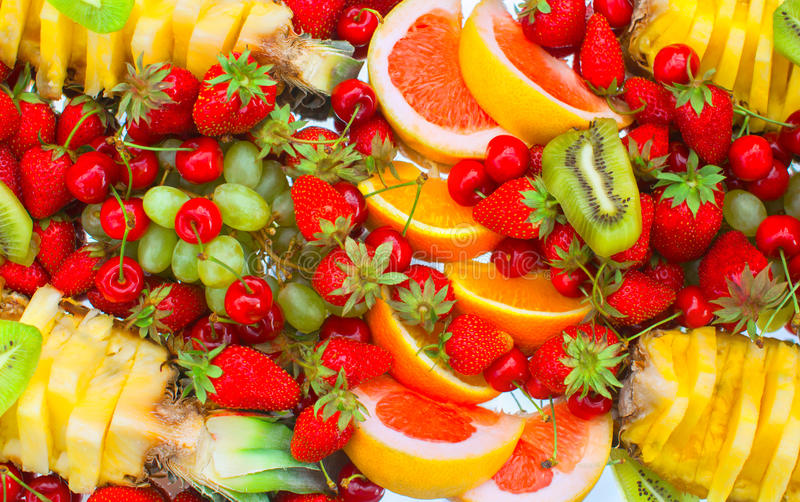 O fruto cortou as laranjas, a banana, o quivi, as cerejas, a toranja, as morangos, as uvas e o abacaxi encontrando-se em uma plac fotos de stock royalty free