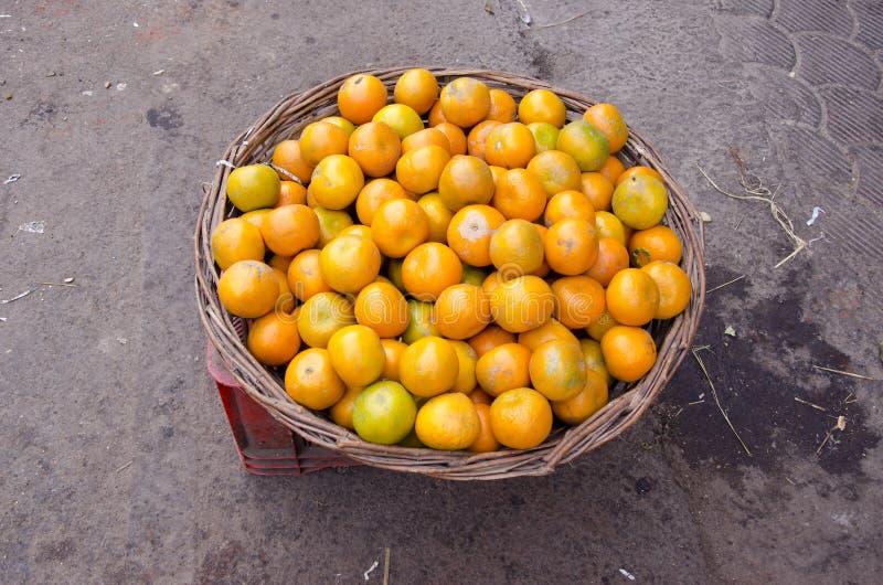 O fruto da tangerina woden dentro a cesta má no mercado de Deli, Índia foto de stock