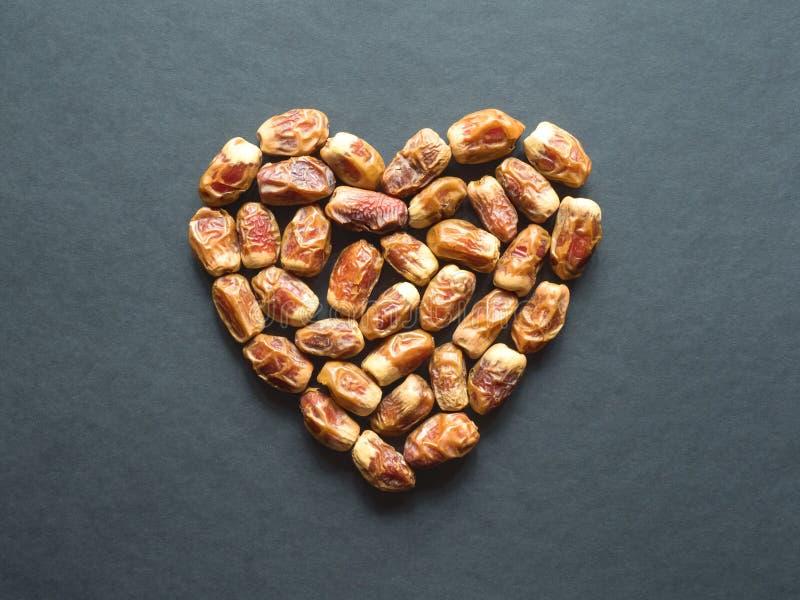O fruto das datas é apresentado na forma de um coração em uma tabela preta imagens de stock royalty free