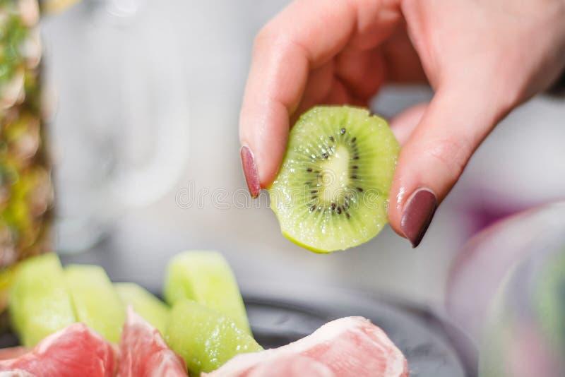 O fruto de quivi descascado verde guarda a mão da mulher fotografia de stock royalty free