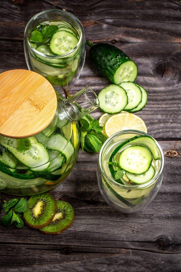 O fruto e as ervas infundiram a água do sassi para a desintoxicação, comer saudável em umas garrafas Vista superior Alimento saud fotografia de stock