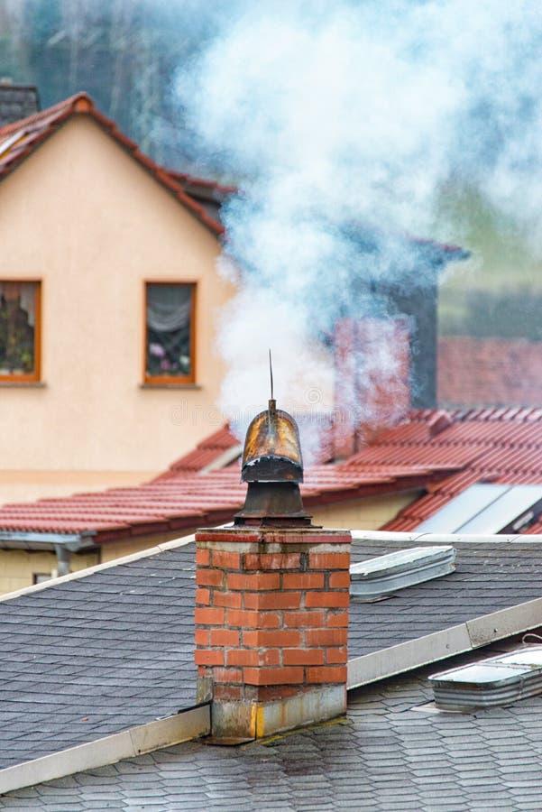 O fumo branco aumenta da chaminé e tira sobre os telhados imagens de stock