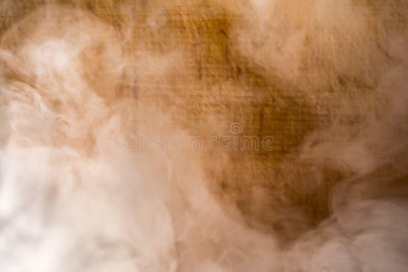 O fumo cinzento no fundo marrom da prancha, borra o fundo abstrato imagens de stock royalty free