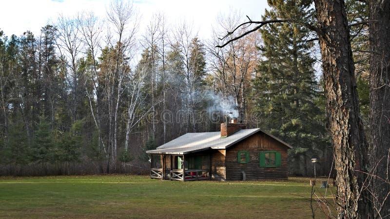 O fumo da chaminé aumenta da chaminé de uma cabine rústica acolhedor fotos de stock royalty free