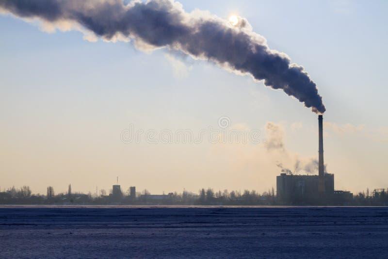 O fumo escuro aumenta da tubulação e fecha o sol foto de stock royalty free