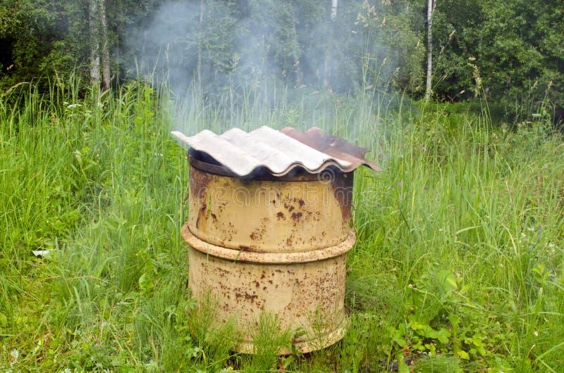 O fumo levantado-se telhado de ardósia asbestino do smokehouse oxidado imagem de stock royalty free