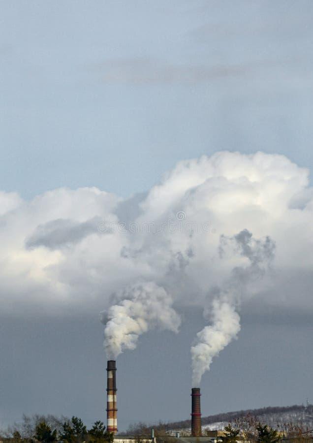 O fumo vem para baixo das tubulações de centrais elétricas térmicos imagem de stock