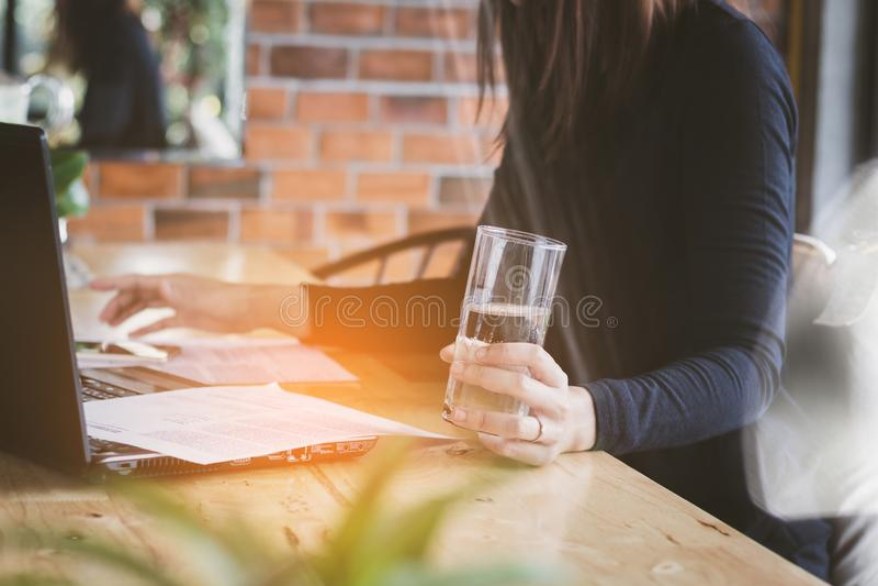 O funcionamento da mulher de negócio de Ásia, água potável com relaxa, divertimento e feliz no escritório imagem de stock royalty free