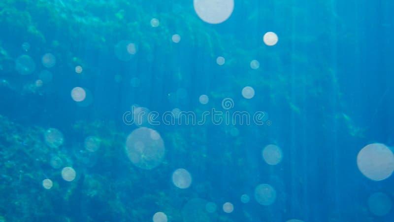 O fundo azul brilhante da água com lente alarga-se fotos de stock royalty free