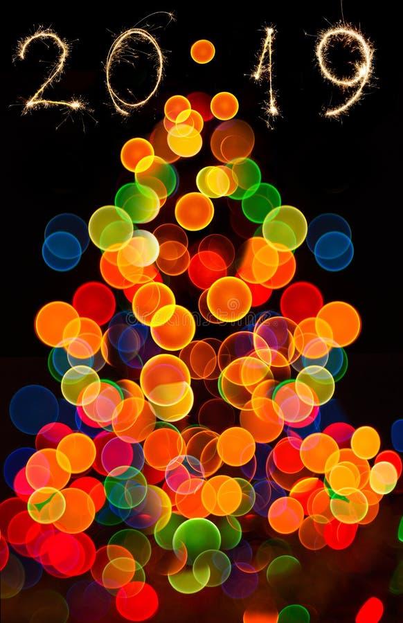 O fundo circular abstrato do bokeh do ight da árvore de Natal e dos 2019 anos escreveu com fogos de artifício do chuveirinho fotografia de stock