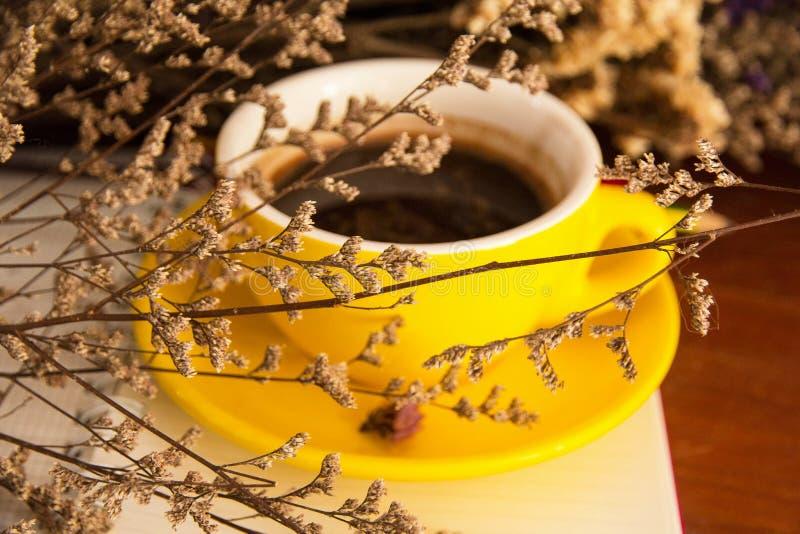 O fundo claro obscuro do projeto do copo de café cerâmico amarelo pôs na parte traseira da flor secada fotografia de stock