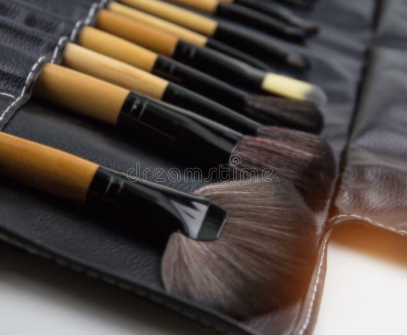 O fundo claro obscuro do projeto do grupo de escova cosmético posto na caixa de couro preta, para compõe, grupo de escova profiss foto de stock royalty free