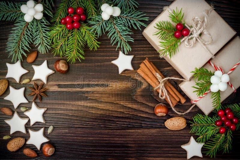 O fundo com cookies do pão-de-espécie, abeto do Natal ramifica e apresenta em umas caixas na placa de madeira velha Copie o espaç fotografia de stock royalty free
