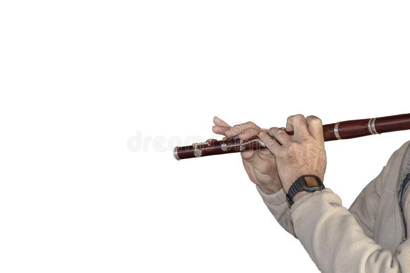 O fundo da música - isolado em branco - homem superior irreconhecível colhido no pulôver do velo joga uma flauta foto de stock